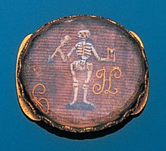 A 17th century hairwork, enamel, rock crystal and gold memento mori slide, probably English, circa 1680  The oval plaque of woven hair with a black and white enamel skeleton holding an arrow and an hourglass, between the initials `J` and `H` in corded gold wire, beneath a faceted rock crystal, the whole collet-set in a gold closed-back mount with twin loops to reverse, dimensions 2.1 x 1.9cm.