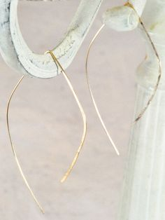 Thin wire is formed into a flattering asymmetric leaf-like shape, then hammered out at one end for a light-catching effect. A delicate style that makes an elegant statement. - Available in sterling si