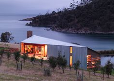 clad in galvanised, corrugated iron, shearer's quarters is positioned on the site of an old shearing shed alongside a timber-clad cottage, north bruny island, tasmania by john wardle architects
