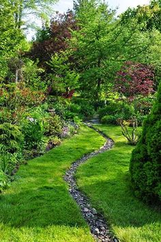 Here is a great example of how you can do so much with so little. Tend to your garden, liven it up with some colorful plants and lush trees, and dig a narrow trench to fill with rocks for your dry creek river. Simple, effective, and unique.