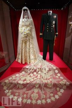 Wedding ensembles of Queen Elizabeth II and Prince Philip, English, 1947. Elizabeth's wedding gown was designed by Norman Hartnell (who also designed her coronation gown) and made of duchesse satin embroidered with 10,000 seed pearls and crystal beads in garlands of star-shaped lily heads, white York roses with orange blossoms, and the heads of wheat (a symbol of fertility). All the embroidery was duplicated on the 15-foot silk tulle train. The veil was made of embroidered tulle, so as not to...