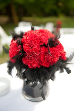 Red carnations with black feather arrangement.  you could do this in white carnation.