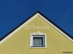 Ockergelbe Fassade mit spitzem Giebel und kleinem Fenster vor blauem Himmel in Burgheim