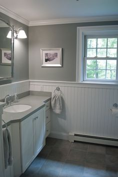 New England bathroom design. Custom by PNB. Porcelain stone look tile, white beadboard wainscot, gray walls, white trim, solid surface countertop with integral bowl, chrome fixtures.