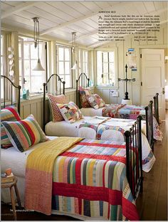 love the variety of quilts in this shared room...and the plank ceiling, and the lights!