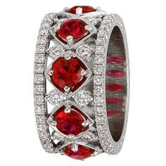 Platinum ruby and diamond band ring, center prong set with five cushion-cut rubies, with round, brilliant-cut diamonds.