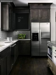 Contemporary kitchen design with espresso stained kitchen cabinets, white quartz counter tops, 'Smoke' gray glass subway tiles backsplash, ivory kitchen island with espresso stained butcher block counter top and chalkboard. Found at https://www.subwaytile