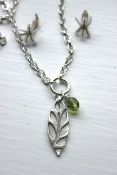 Silver leaf necklace with olive glass drop.