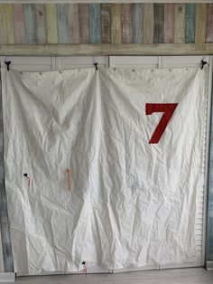 Hand made recycled sail cloth shower curtain with red 7 and tell tales.