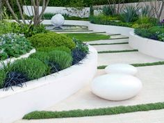This modern white garden uses dramatic lines, sculptures and clusters of colorful ornamental grass to create an inspirational space.