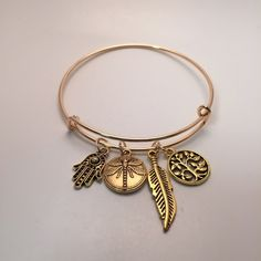 Gold charm bangle New in packaging. Gold colored. 4 charms are attached. Zinc alloy with gold plating Jewelry Bracelets