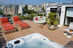 Terrasse sur les toits avec jacuzzi, transats et vue sur la ville.