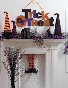 Glitterly orange and purple Halloween mantel decor with witch legs