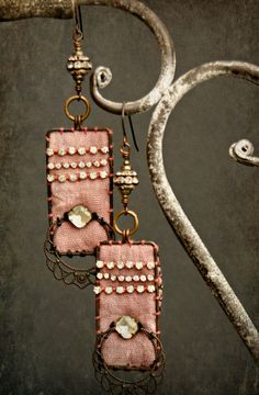 These romantic assemblage earrings combine rhinestone bling, filigree beauty and rustic copper to make a perfect mix of components to create these unique one of a kind earrings.  From top to bottom they feature: oxidized copper earwires a round rhinestone bead a brass jumpring the pink fabric adorned with a few rhinestine chain pieces and square rhinestone bead and a gorgeous black filigree all attached to a handmade copper frame.  The fabric i used is a little rugged, i think that adds to…