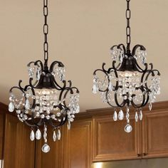 Kitchen lights over island The elegant chandeliers from the Versailles Collection have one (1) light each and are decorated with 100% crystal. The frame is wrought iron with a black finish.
