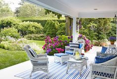 Cottage Style Homes: More vintage pieces are found on the outdoor patio in the form of white wicker chairs. Blue and white fabric continues the color scheme.