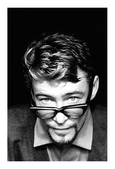 Young Peter O'Toole wearing glasses and a goatee, giving a saucy look to the camera.