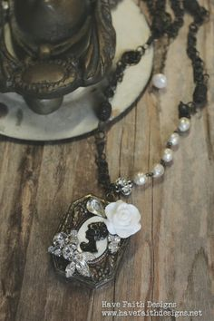 """Maidens Garden A timeless heirloom handcrafted from old and new. Features a stunning opening cameo locket, embellished with flower and rhinestone details. An old pearl strand and ornate vintage chain, 18"""" long"""