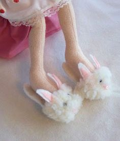 I made these bunny slippers a couple years ago for a cloth doll.  Theyre glued on.  But theres no reason they cant be made for a clay doll or made as removable slippers.  Heres how I made this pair.  Materials: White felt Pink felt or fabric or paint Small piece of white lightweight sheepskin fabric or something fuzzy Pink embroidery floss 2 tiny black beads Small piece of cardboard (cereal box will do)