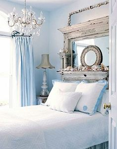 white coastal bedroom with blue accents and chandelier