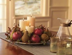 Simple fall centerpiece, with pomegranates, pears, candles, and leaves.