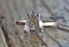 natural clear, rose cut diamond ring with gorgeous clarity and shimmer, and unusual salt + pepper matrix. the perfect unique engagement ring!  -rose-cut pear-shaped diamond -14kt recycled rose gold prong setting  -smooth, matte finish -conflict free diamond weighs 1.12ctw and measures 8 x 7 x 1.5mm deep -band measures 1.5 x 1mm  *contact me for custom stacking ring sets of your choice  *ring is packaged in a black velvet ring box and shipped via FedEx with tracking and full insurance…