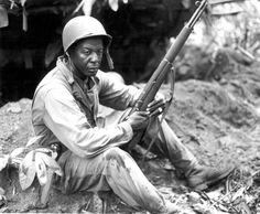 First Sergeant Rance Richardson, a veteran of two world wars, takes a break along the Numa Numa Trail on Bougainville (April 4, 1944). His infantry rifle is an M1 Garand.
