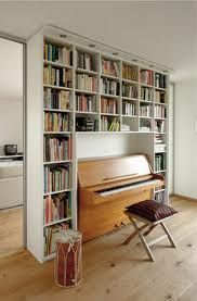 Music room with a wall shelf that doubles as sound proofing with caustic panels on the back of each shelf