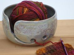 **This item is in stock. Ready to ship within 1~3 days after the order is placed.  This is a pottery yarn bowl with my signature hand carved design. Approx. 3 7/10 tall with a 7 opening. This works great to keep a ball of yarn from rolling on the floor (collecting dust and getting your cats attention...), while you knit or crochet. This one has an extra hole for a two-ball knitter.  It is made with stoneware clay, fired at Cone 6. After the bowl is created on my wheel, the swirly design is…