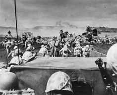 Men of the US 4th Marines rushing out of their landing craft for Iwo Jima landing beach 19 February 1945.