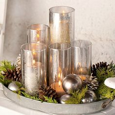 Candle Collection on a silver tray- One of the best places to find outdoor decorating accents? Your kitchen. Take this silver serving tray: It offers the perfect receptacle for a collection of shimmery candleholders, evergreen sprigs, pinecones, and holiday ornaments. To create your own similar setup, tuck in the big items first -- here, orbs and pinecones -- and then fill in empty spaces with greenery.