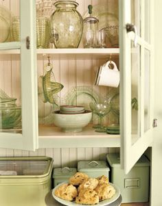 soft green and cream cabinet with green depression glass is in the kitchen of the little green guesthouse