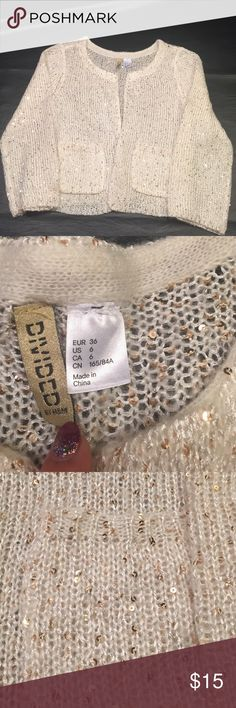 Cream and gold sequined cardigan Lose knit cardigan. Gold sequins add a small sparkle. Two pockets no buttons. Divided Sweaters Cardigans