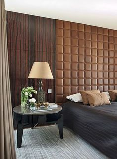 Powerful Midcentury influence. Splendorous tiled leather headboard and wood cover walls. This is the perfect bedroom masculine design