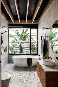 In the bathroom, tiles cover the walls, while a freestanding bathtub is positioned beneath the window, and a minimalist glass shower screen allows the natural light from the window to filter throughout the room. #ModernBathroom #BathroomDesign #TiledWalls