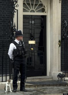 A police officer stands alongside 'Larry' the Downing Street cat outside Number 10 Downing Street in London, June 21, 2012, b
