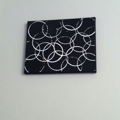 Circles on canvas! Paint the dollars store canvas black then take the ring of a mason jar or a glass and dip in white paint. Easy bathroom decor! Matches my shower curtain