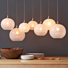Go global. Our Glass Orb Chandelier shimmers with seven opal-glass globes that hang from a satin nickel frame. The globes are adjustable in height, creating a dramatic atmosphere in the kitchen, dining room and beyond.