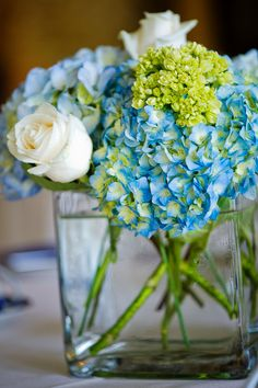 Blue Centerpieces-I like this. Simple and elegant. The rose also adds some definition to the centerpiece. The touch of green also adds to the color pop. Of course, there's already green in the stems. Like!