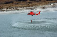 A Coast Guard helicopter drops a buoy