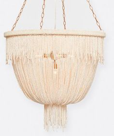Coco beads are loosely draped and gathered in this glamorous chandelier. Accented with sparkly clear beads, the Carmen Chandelier by Made Goods has an undeniable sexy appeal that is even more desirable since it doesn't try too hard!
