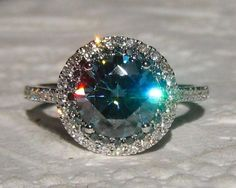 A beautiful and bligny engagement ring featuring a sparkly blue moissanite with white and blue diamonds double halo.  The center stone is a 8mm