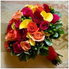 hand-tied bouquet of yellow calla lilies, mixed with red, peach and orange roses.  Green hypericum berries as foliage.