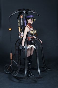 Steampunk Cage Skirt Transport - Steel cage skirt with penny-farthing wheel, parasol, steam gauge bra, goggles, hat and boots - For costume tutorials, clothing guide, fashion inspiration photo gallery, calendar of Steampunk events, & more, visit SteampunkFashionGuide.com