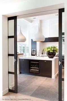 Ook een idee voor de deuren die de woonkamer van de eetkeuken scheiden: schuifdeuren. Alleen kan de deur aan de tuinzijde nergens in geschoven worden...