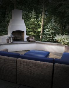 Simple stucco fireplace blends with with colonial. Pops of blue furniture add color and elegance. Stucco Fireplace, Stucco Walls, Fireplace Wall, Fireplace Outdoor, Fireplace Ideas, Outdoor Spaces, Outdoor Living, Outdoor Decor, Blue Furniture