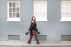 Anisa Sojka styles orange, white and black striped Dorothy Perkins wide leg trousers and matching sleeveless vest | Off the shoulder crochet top | Brown gladiator shoes with wooden heel | Gold stackable rings | Straight brunette hair let loose | Fashion blogger street style shot in London by Victoria Metaxas