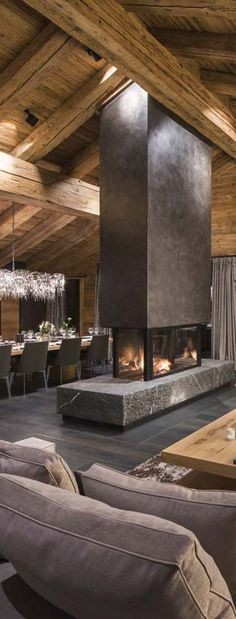 PIN5. Rustic design of the living/dining area in the house. Timber ceiling with large beams and fireplace work in unison to create this warm and inviting atmosphere in the area.