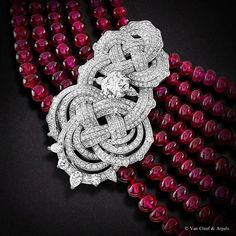Detail of the Beauté Eternelle necklace, Palais de la chance collection  White gold, diamonds, 665 ruby beads from Madagascar and two EVVS2 round diamonds od 2,31 and 2,33 carats.   The Beauté Eternelle necklace from the Palais de la chance collection is inspired by the panchang, a popular lucky charm in China. This endless motif is  associated with long life and prosperity. The intertwined diamonds represent the panchang knot. Discover the unique skills applied by Van Cleef