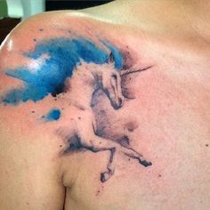 Beautifully inked unicorn tattoo on the shoulder. The style is that of a washed out watercolor painting where the unicorn is seen running wild and free.